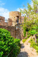Fototapete - Castle walls and green alley in old town of Tossa de Mar, Costa Brava, Spain