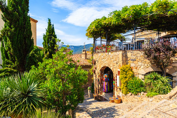 Fototapete - Shop with tourist souvenirs in narrow street with stone houses in old town of Tossa de Mar, Costa Brava, Spain