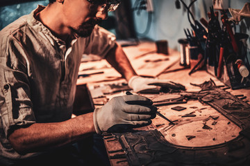 Pensive craftman is restoring ancient broken stained glass at his own workplace.