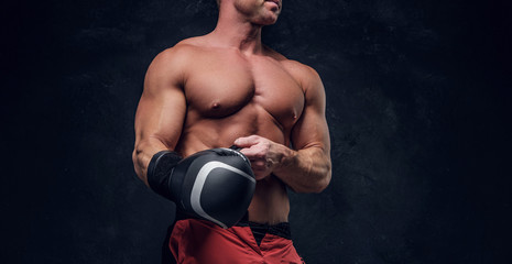 Serious muskular man get prepared for boxing, his is wearing his boxer gloves.
