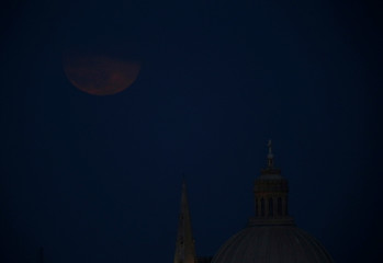 The Strawberry full moon rises behind the church spire of St Paul's Anglican Pro-Cathedral and the dome of the Basilica of Our Lady of Mount Carmel in Valletta