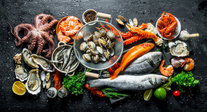 Variety of fresh seafood with herbs and lime.