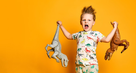 little cheerful boy holds a plastic dinosaur in each hand. The boy is dressed in a suit with pictures of dinosaurs.