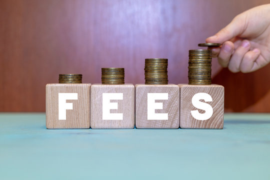 Fees Hidden Service Business concept. Hand puts coin on growing coins stack on wooden blocks with fees word. Cost, fee and taxes.