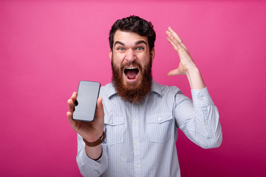 Blow your mind concept. Young bearded man showing smartphone blank display, gesturing with his hand near his head.