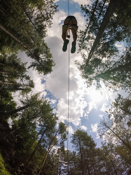 Aerial view of a person crossing the forest through a large zip line cable.