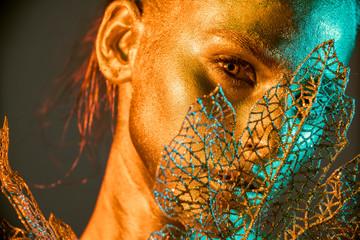Fashion model woman golden skin face in bright sparkles, Trendy glowing gold skin make-up. Glitter metallic shine makeup