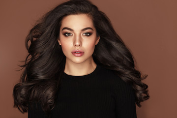 Brunette haired Woman Portrait with blue eyes and Healthy Long Shiny Wavy hairstyle. Volume shampoo. Black Curly permed Hair and bright makeup.  Beauty salon and haircare concept. Wall mural