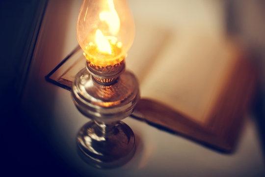 Vintage kerosene lamp and old open book