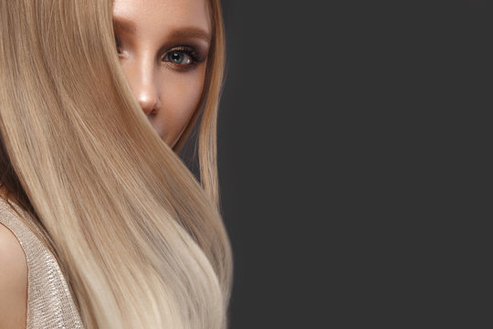 Beautiful blond girl in move with a perfectly smooth hair, and classic make-up. Beauty face.