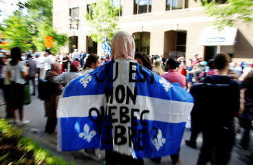 "A woman holds a flag with the slogan ""Where is my free Quebec"" while protesting Quebec's new Bill 21 in Montreal"
