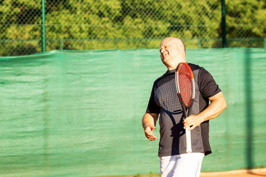 A middle-aged bald man emotionally plays tennis on the court. Loses the opponent. Outdoor.