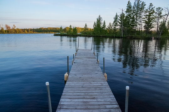 Pier jutting out into the Chippewa Flowage in front of a wooded island in the Northwoods