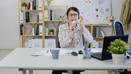 Pretty asian girl fashion designer singing in office using cellphone as microphone having fun smiling. carefree joyful happy lady worker in glasses wearing headphones enjoy music with smart phone.
