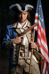 Portrait of man dressed as soldier of War of Independence United States aims from pistol with flag. 4 july independence day of USA concept photo composition: soldier and flag.