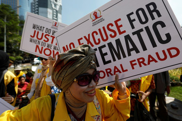 A woman carries a placard as she takes part in a rally near Indonesia's constitutional court in Jakarta