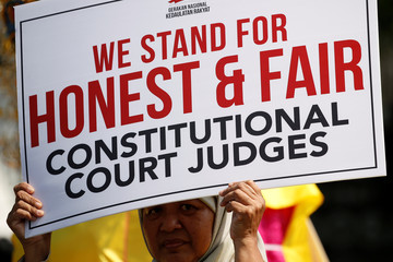 A woman holds a placard as she takes part in a rally near Indonesia's constitutional court in Jakarta