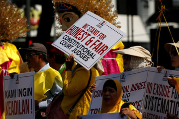 A woman covers her face with a placard as she takes part in a rally near Indonesia's constitutional court in Jakarta
