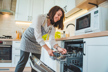 young pretty woman putting dishes in dishwasher