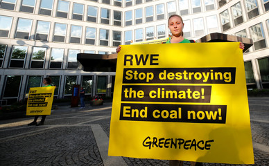 Greenpeace activists hold signs while protesting against climate change in front of the headquarters of German utility RWE in Essen