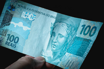 Man holding a hundred note ( Cem reais ) . Brazilian currency.