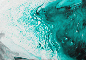 photography of abstract marbleized effect background. black, light turquoise and white creative colors. Beautiful paint