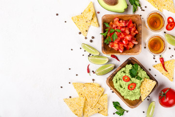Mexican food selection: sauce guacamole, salsa, chips and tequila shots with lime on white...