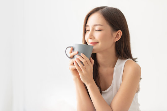 Attractive girl is holding a grey mug.