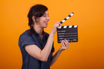 Beautiful young woman with cinema clapper standing in front of wonderfulyellow background