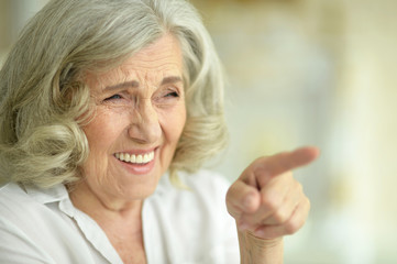 Emotional happy senior woman posing at home