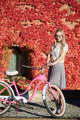 Young pretty long-haired happy blond woman in casual clothing and glasses, standing at pink lady bicycle on bright warm sunny day on background of brick wall overgrown with beautiful red ivy leaves.