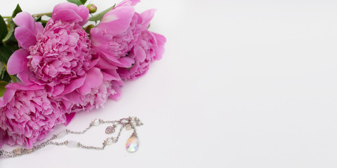 Beautiful pink peony flowers with jewellery on white  table with copy space for your text top view and flat lay style.