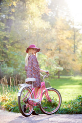 Slim blond fashionable long-haired attractive girl in glasses, short dress and pink hat at lady bicycle outdoors on paved sunny summer park alley on beautiful foggy green and golden trees background.