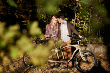 Happy romantic couple, bearded man and attractive girl close together at tandem double bicycle outdoors in dark autumn park or forest on sunny clearing in the evening