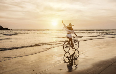 Happiness woman traveler with her bicycle rides on sea coastline