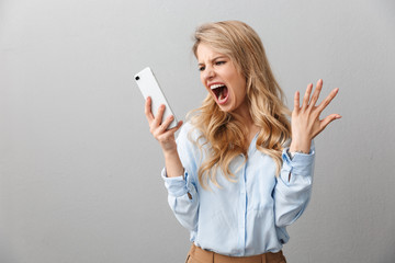 Photo of angry puzzled businesswoman with long curly hair worrying and screaming while calling on smartphone