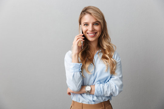 Photo of successful blond businesswoman with long curly hair smiling and calling on smartphone