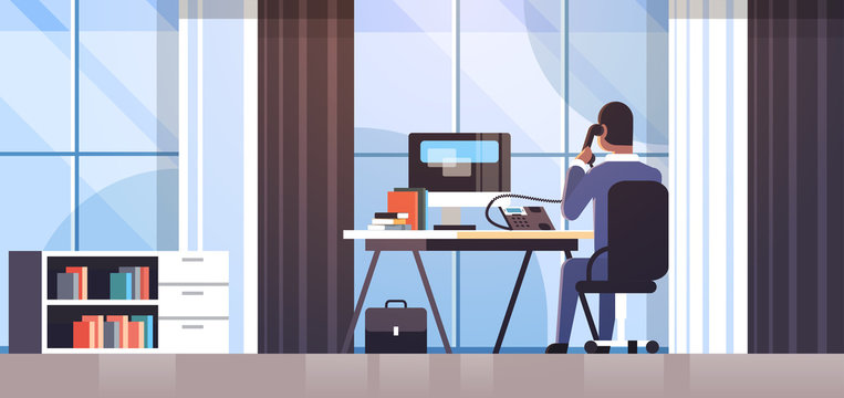businessman sitting at workplace desk rear view business man using computer while talking on landline phone working process concept creative office interior flat horizontal