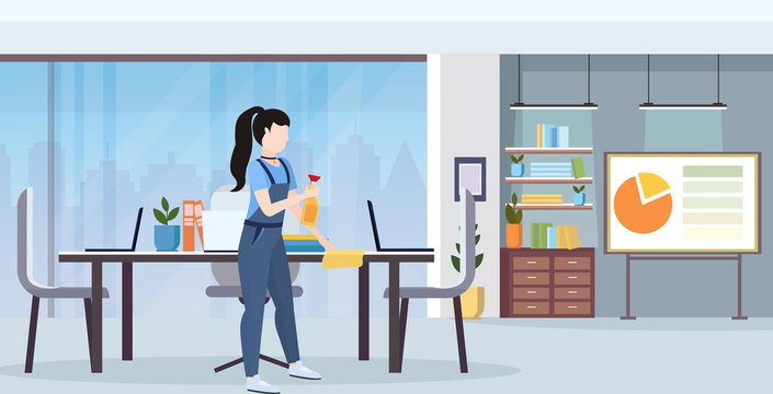 female janitor in uniform wiping conference table by dust cloth cleaning service concept full length flat modern office interior horizontal