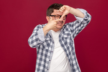 Portrait of attentive handsome middle aged business man in casual checkered shirt, eyeglasses standing with crop hands composition and looking at target. studio shot, isolated on dark red background.