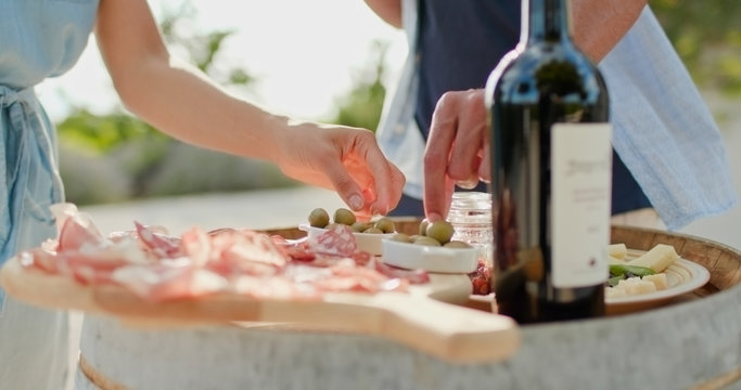 Romantic couple, man and woman toasting with red wine and eating finger food appetizer at warm sunset.Food detail shot. Friends italian trip in Umbria.4k slow motion