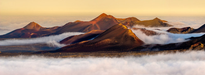 Fotobehang Canarische Eilanden Volcanoes in the Timanfaya national park on Lanzarote. Volcanoes rising out of the clouds