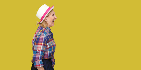 Profile side view portrait of angry modern stylish mature woman in casual style with hat standing, looking forward and screaming. indoor studio shot isolated on yellow background.