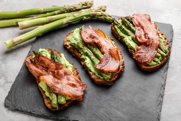 Tasty toasts with bacon on slate plate