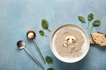 Bowl with delicious mushroom cream soup on color background
