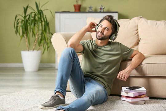 Young man listening to audiobook at home