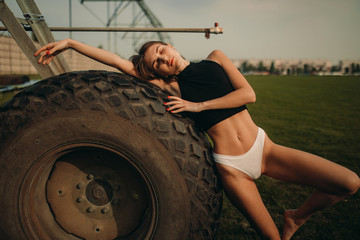A young woman is standing next to a big wheel of agricultural sprayer.