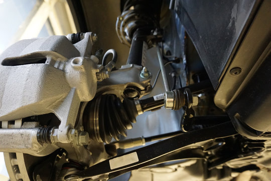 Sharp technical photograph.  The design and elements of a modern car. Front suspension. Shock absorber. Suspension arm of a vehicle. Drive shaft.
