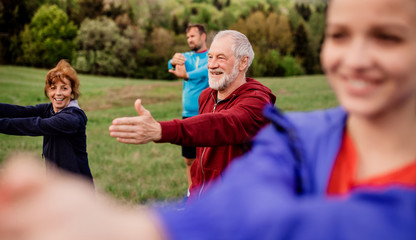 Large group of fit and active people doing exercise in nature, stretching. Papier Peint