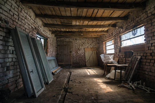 Old barn interior in the village. Vintage shed built of wood and brick, abandoned barn. Inside of a rustic stable